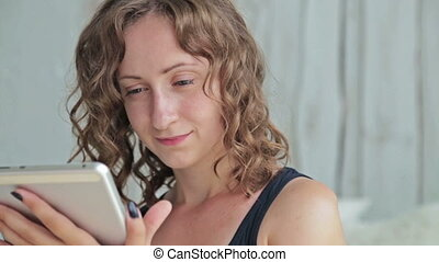 Young curly woman sitting on bed with tablet pc. Dolly shot...