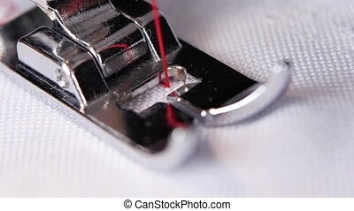 Sewing machine makes a red thread stitch in slow motion