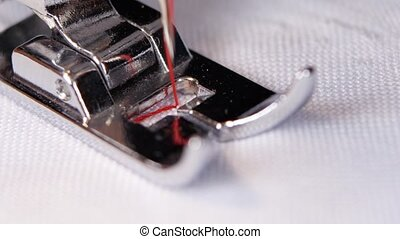 Sewing machine sews a white cloth black thread. Macro