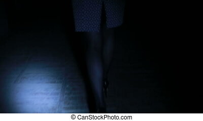 female legs in high heels are on the dark corridor - Girl on...