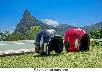 Red and black motorcycle helmets lying on the grass on the...