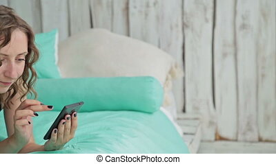Young curly woman lying in the bed with smartphone. Dolly...