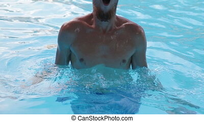 a young man with a beard dives and comes up with a splash in the pool with clear blue water