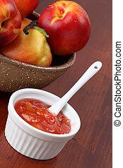 Nectarine jam in a white bowl and fresh nectarines