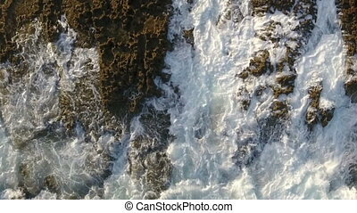 Aerial. The magic wave motion on the rocks, view from the...