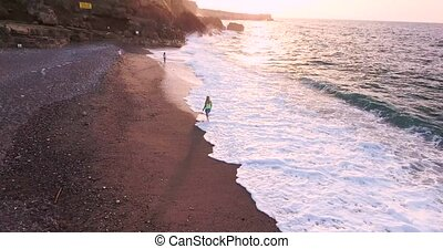 woman walking along beach with beautigul waves at sunset...