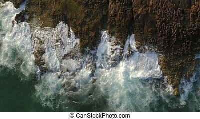 Aerial. Slow motion of the sea on the rocks, view from the...