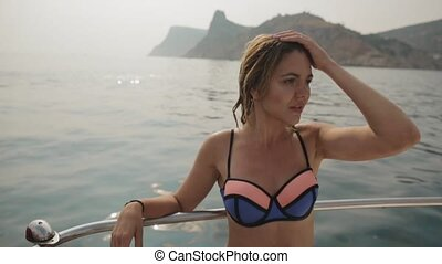 Attractive young woman with wet hair in bikini sitting on a yacht at sea