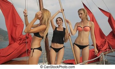 Gorgeous young women in bikinis dancing on the deck of a yacht with red sails