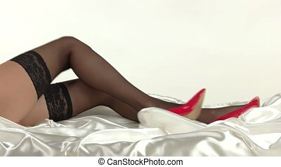 Legs with high heels lying. Stockings and red shoes. Secrets...
