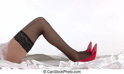 Legs wearing red heels. Stockings with lace. Simple rules of...