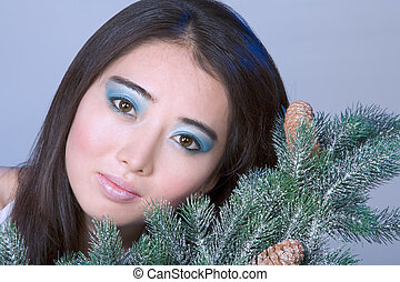 Winter portrait 1 - Asian girl by branches of Christmas tree...