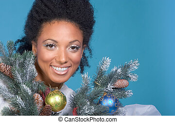 Christmas portrait - Attractive female by decorated branches...