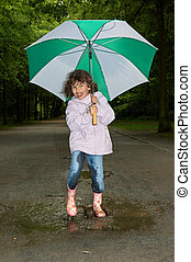 Umbrella dance - Little girl dancing with her umbrella in a...