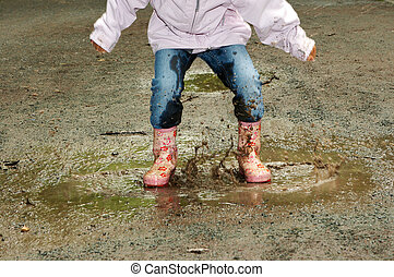 Both feet in the puddle - Feet of a little girl jumping into...