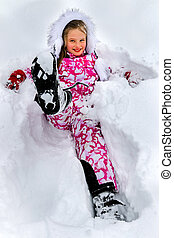 Little girl wearing winter clothes lying in deep snow .