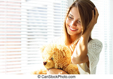 Smiling girl sitting by the window