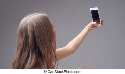 young blonde girl holding smartphone and taking selfie