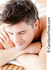 Portrait of a smiling man lying on a massage table