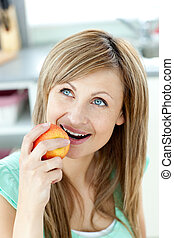 beautiful girl eating an apple looking at the top in her...