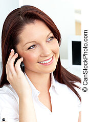 Bright caucasian businesswoman talking on phone with her cellphone sitting in her office