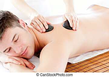 Positive young man enjoying a back massage with hot stone in...
