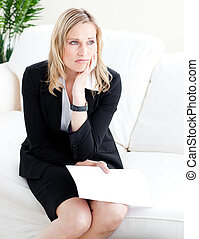 Frustrated businesswoman holding a paper sitting on the sofa