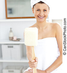 Merry woman holding a brush smiling at the camera