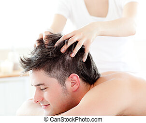 Happy young man receiving a head massage in a spa center