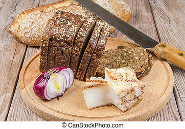 rye bread with bacon and red onion on a cutting board