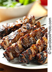 Chicken Kebabs - Barbecued chicken kebabs on a platter, with...