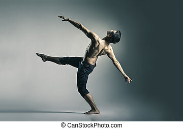 Young and stylish modern ballet dancer on grey background