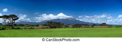Peaceful green lawn with a cove of volcano covered by a snow...