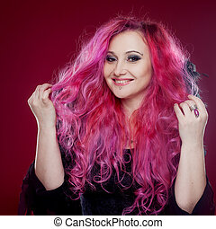 Smiling woman with pink hair in witch image. Halloween style