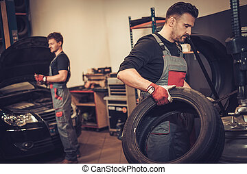 Professional car mechanic replace tire on wheel in auto...