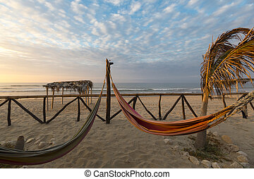 Romantic cozy hammocks with sunset on the beach, Punta Sal, Peru