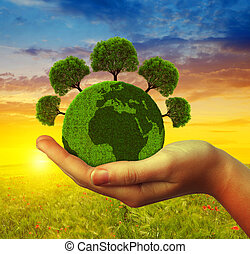Hand holding green planet with trees at sunset. Concept of...