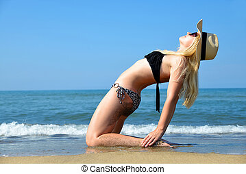 Young woman stretching body on sandy beach.