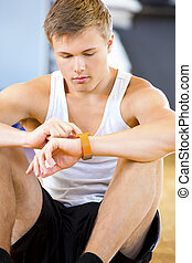 Man Using Smart Watch While Sitting In Gym - Handsome young...