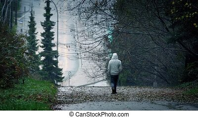 Man Walking Down Hill On Rainy Day - Man walks down slope to...