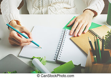 Woman writing in spiral notepad closeup - Woman with various...