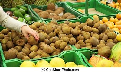 man picks fruit kiwi in the supermarket