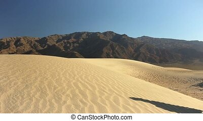 woman climbing a sand dune in the death valley