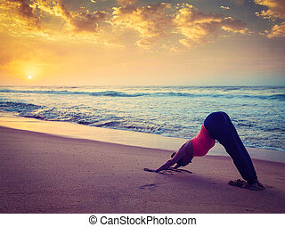 Young sporty fit woman doing yoga at beach on sunset -...