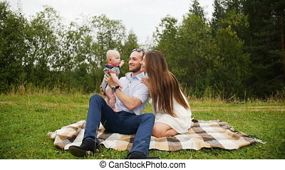 Happy family parents playing with baby during picnic in park