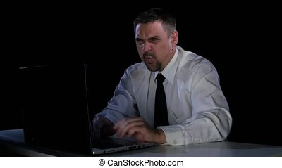 Emotions rage. A man sitting at his laptop in anger -...