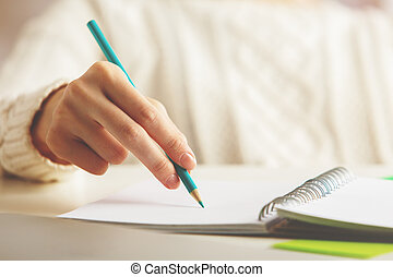 Female writing in spiral notepad - Close up of female hand...