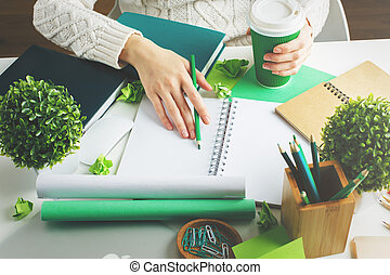Woman with coffee writing in notepad - Woman holding green...