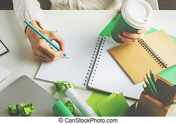 Female with coffee writing in notepad - Female holding green...
