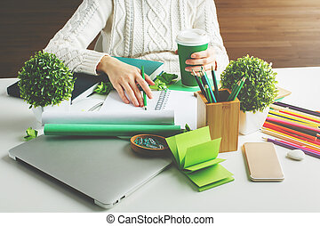 Girl with coffee writing in notepad - Girl hodling green...